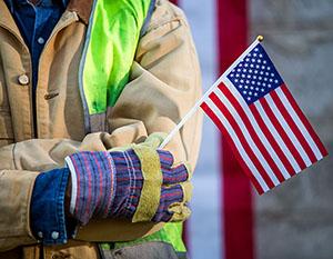 Worker holding US flag