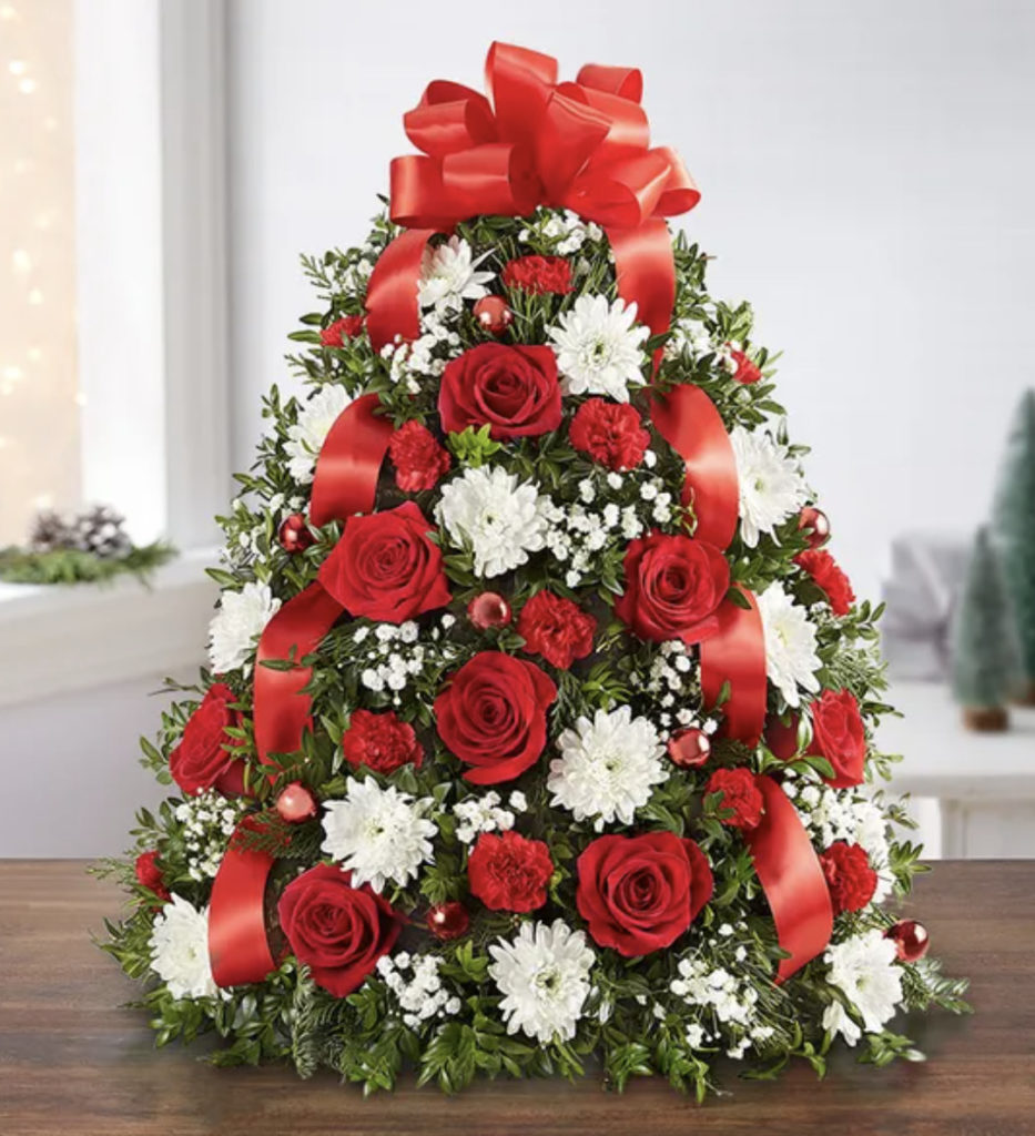 A photo of a Christmas tree made out of flowers.