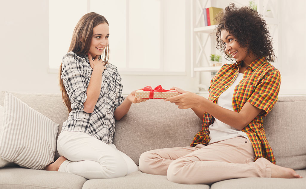 Woman giving gift to friend