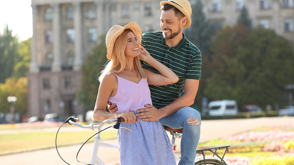Happy couple with bicycle outdoors on summer day