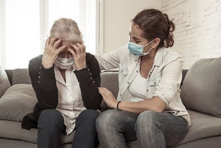 Woman wearing mask comforting older woman