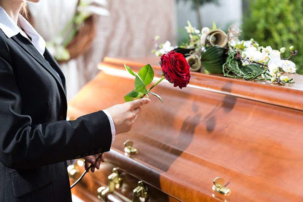 Holding rose near casket