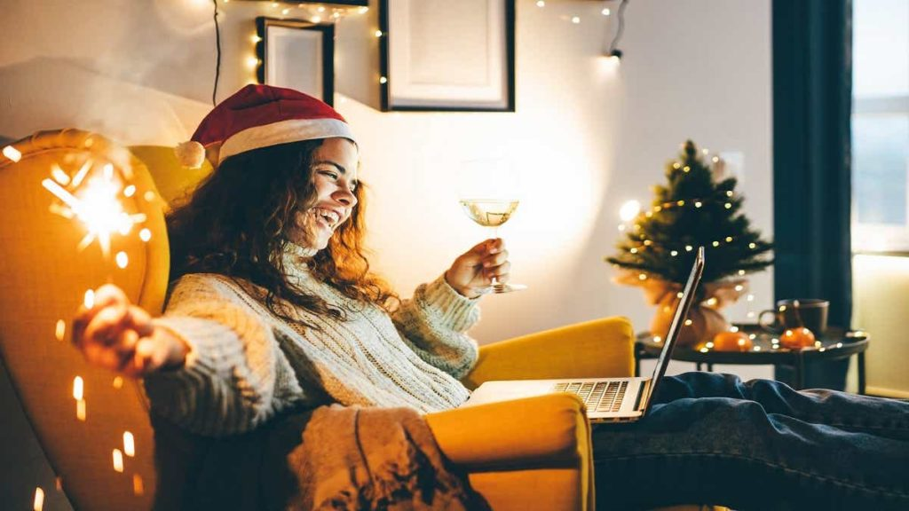 Happy young woman wearing Santa hat, drinking champagne, talking with friends on video call celebrate New Year party.