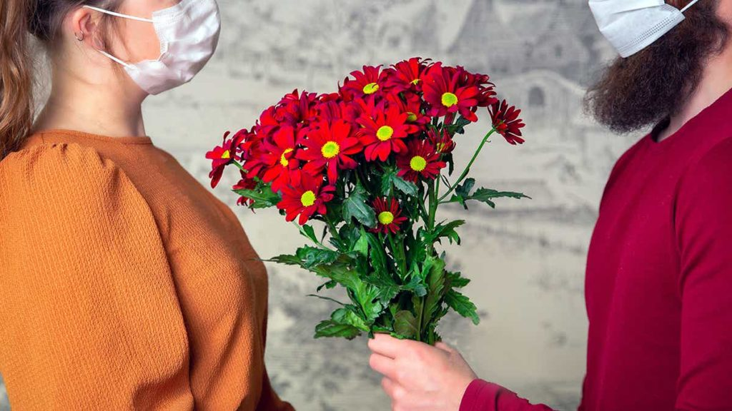 Man giving woman flowers wearing a mask
