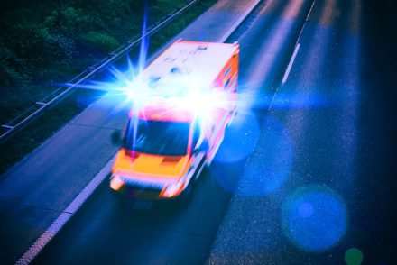 An ambulance drives with lights flashing on a highway