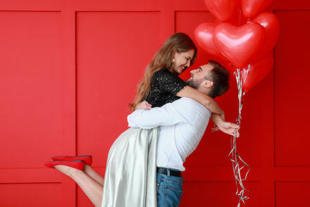 Man holding woman with heart balloons