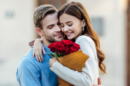 Couple embraces with bouquet of roses