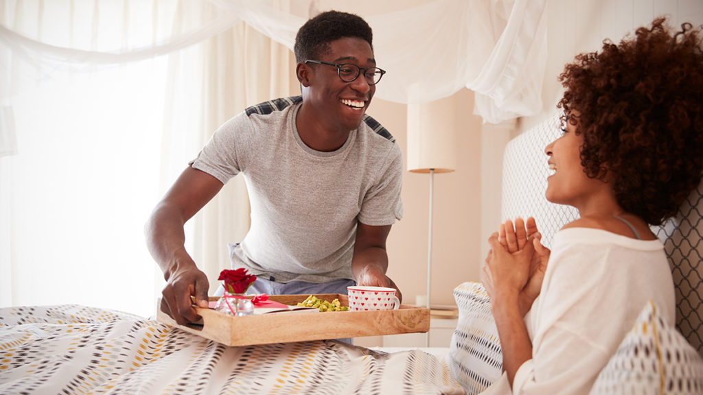 Man giving woman breakfast in bed