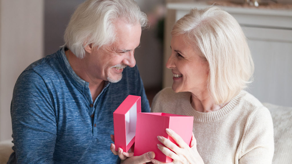 Senior couple with gift in pink box