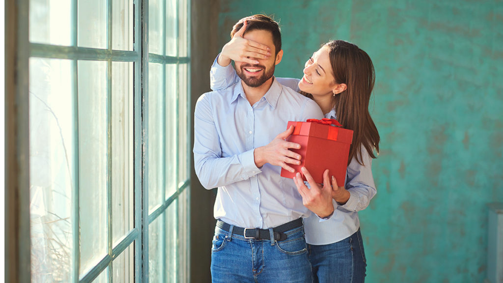 Woman surprising man with gift in red box