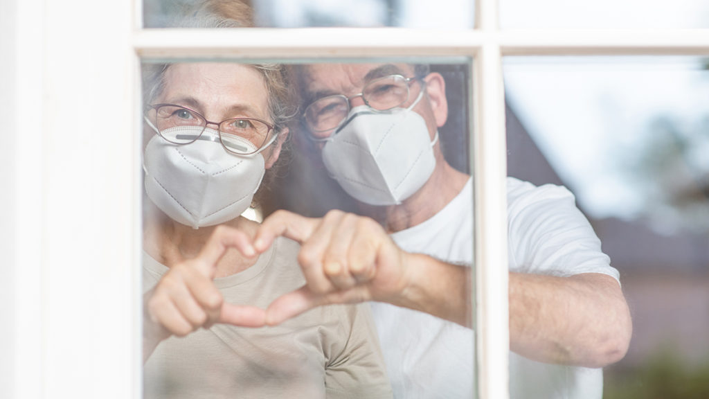 Old couple wearing masks making heart shape with fingers
