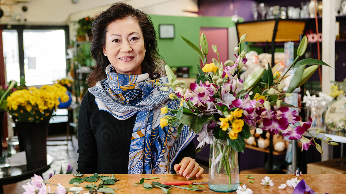 Photo of local florist Vivian Chang and an arrangement