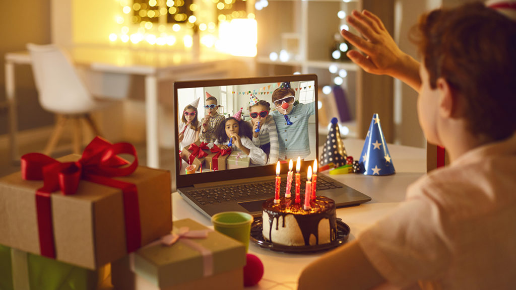 Boy with cake waving to friends on video call