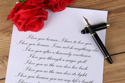 A photo showing a love poem with a fountain pen and roses