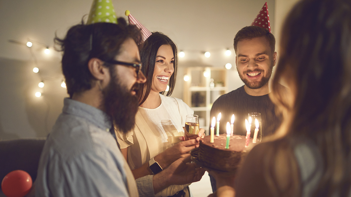 Group of people celebrating a birthday with cake and hats