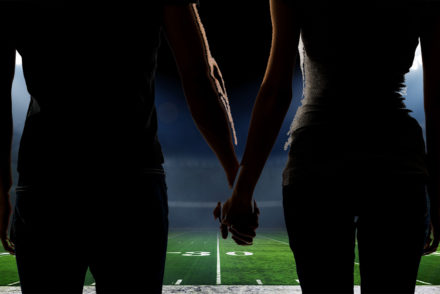 A couple holds hands on the 50-yard line of an American football stadium