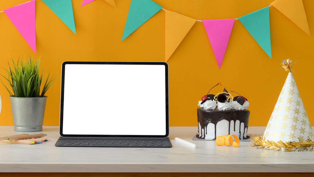 Laptop surrounded by birthday decor