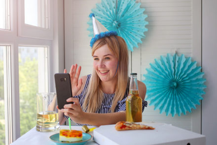 Woman taking selfie wearing birthday hat