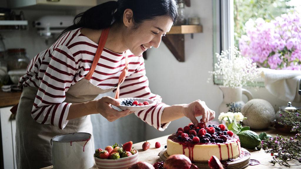 Woman making berry cheesecake