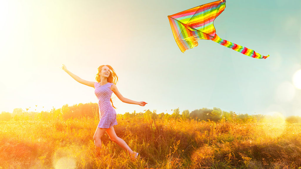 Woman running with a kite