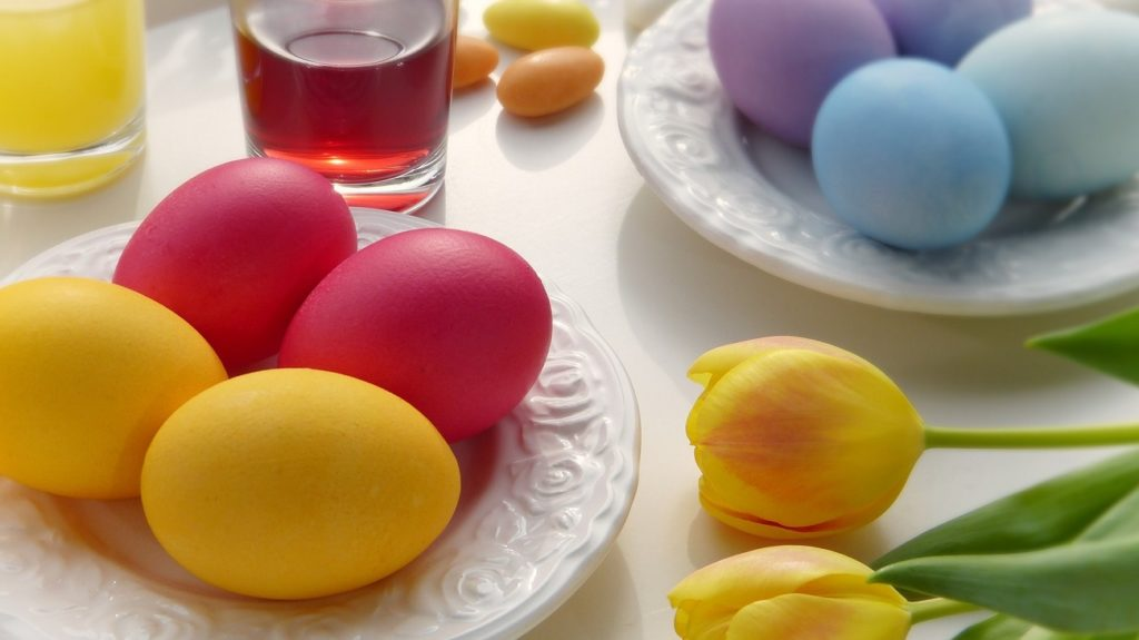 Easter eggs and tulips on table