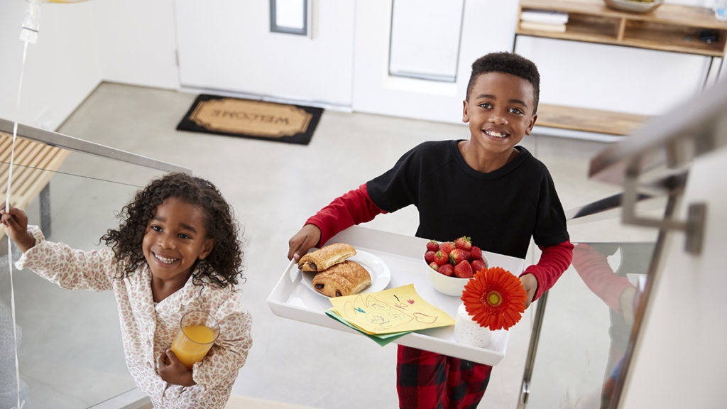 Boy and girl bringing mom breakfast in bed