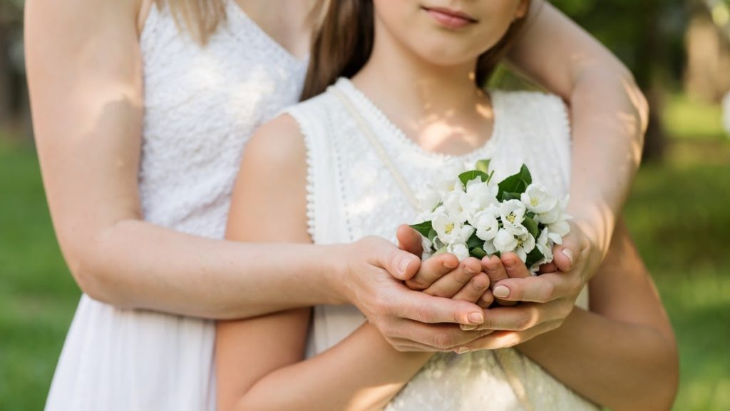 Girl and mom in white dresses with flowers