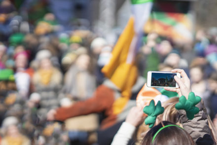 A photo of a woman holding a smartphone while celebrating St. Patrick's Day