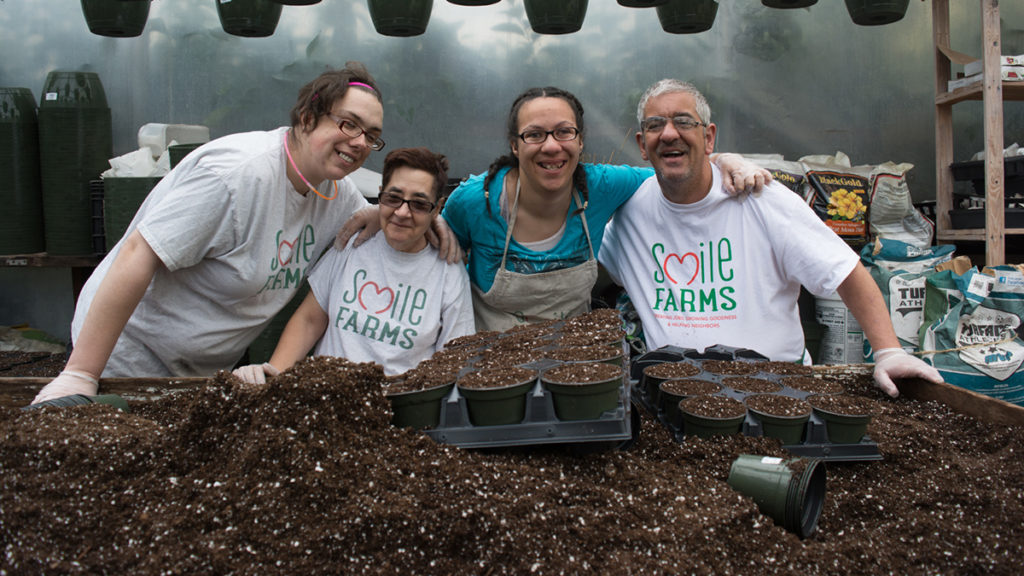 Farmers at Smile Farms pose in front of a planting bed