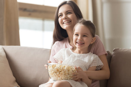 Happy mom and girl laughing watching tv on sofa