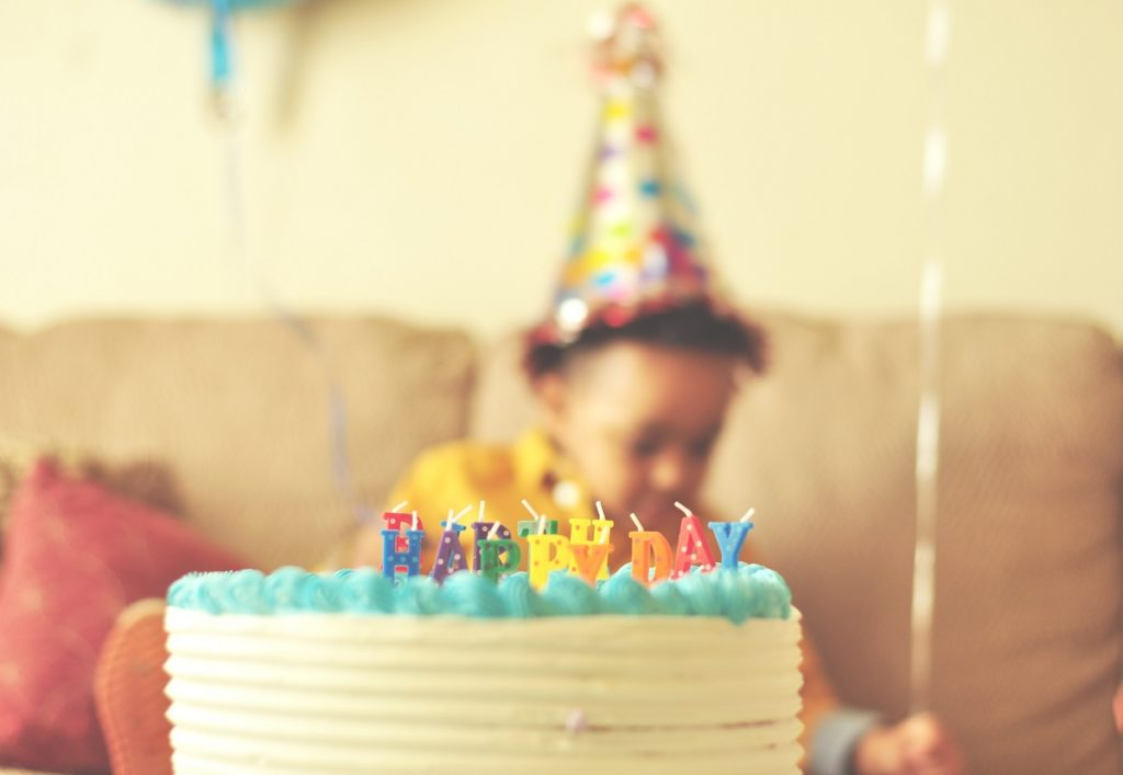 Blowing out candles is one of the most popular birthday traditions. In this image, a young boy gets ready to make his wish.