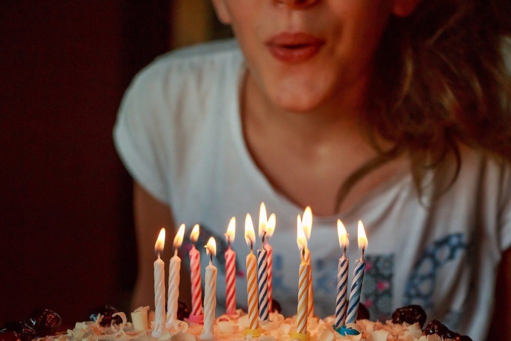 Blowing out candles is one of the most popular birthday traditions. In this image, a young woman gets ready to make her wish.