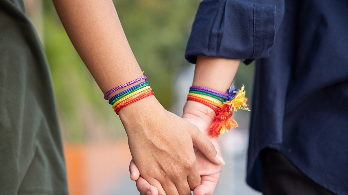 Two women holding hands adorned with rainbow bracelets