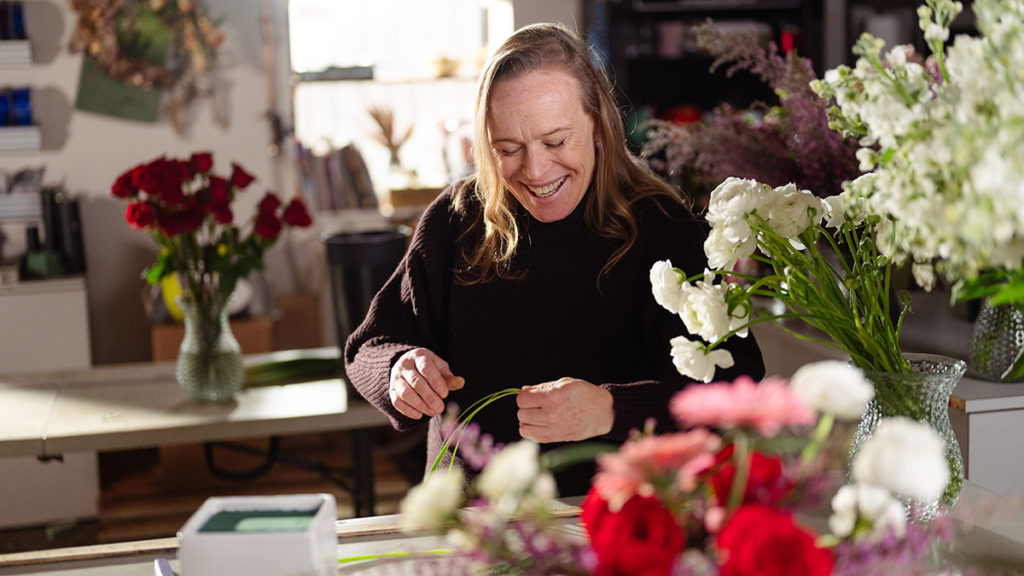 A photo of local florist Patti Fowler inspecting flowers