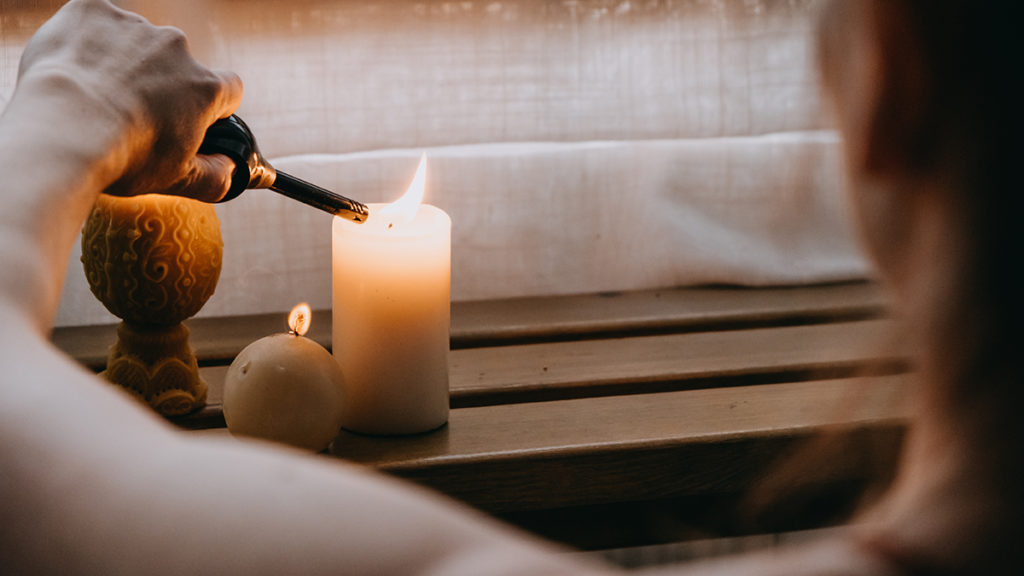Photo of woman lighting a candle in relaxing setting