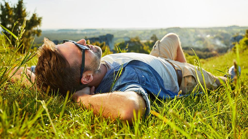 Photo of man lying on grass enjoying peaceful sunny day