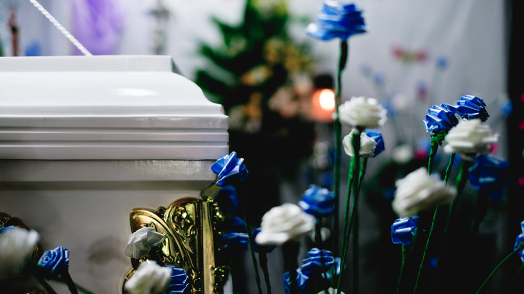 A photo of flowers next to a white casket