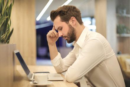 Photo of man looking at laptop