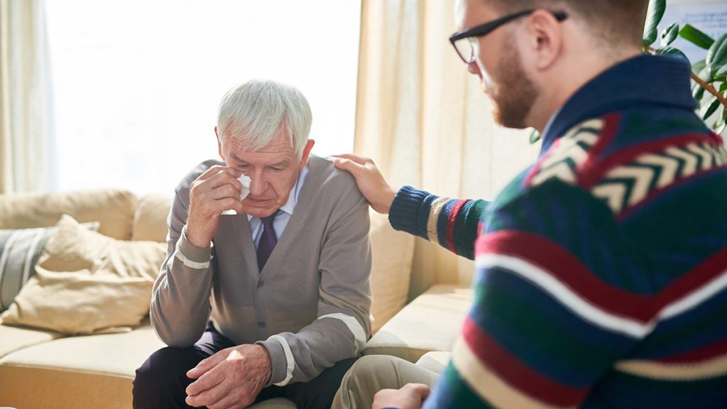 Photo of empathetic psychologist consoling man and stroking his shoulder while supporting him and cheering up during therapy session