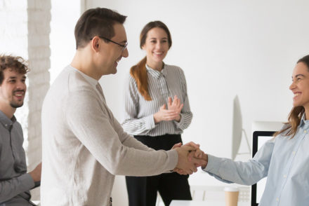 Photo of manager showing employee appreciation to worker