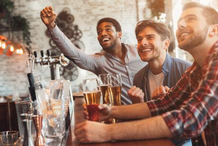 Men at bar watching TV