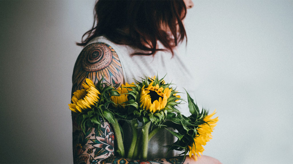 The sunflower is a popular flower tattoo. In this photo, a woman holds a bouquet of sunflowers against her tattoo of the flower. Sunflowers are commonly associated with good luck, happiness, and new beginnings.
