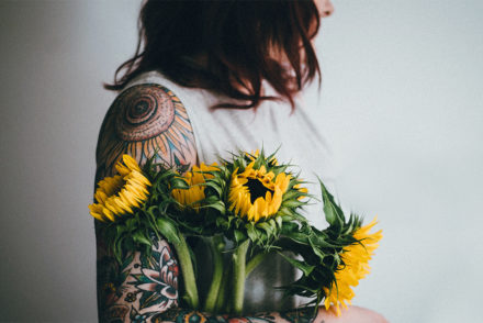 Photo of a woman holding sunflowers next to her flower tattoo