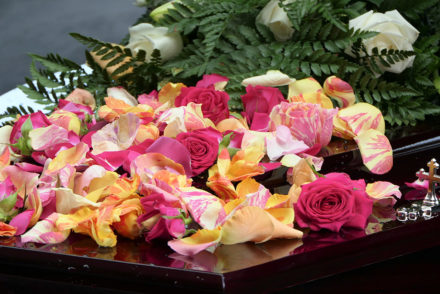 Floral arrangements for a funeral should be colorful and joyful. This photo shows yellow and red flowers atop a casket.