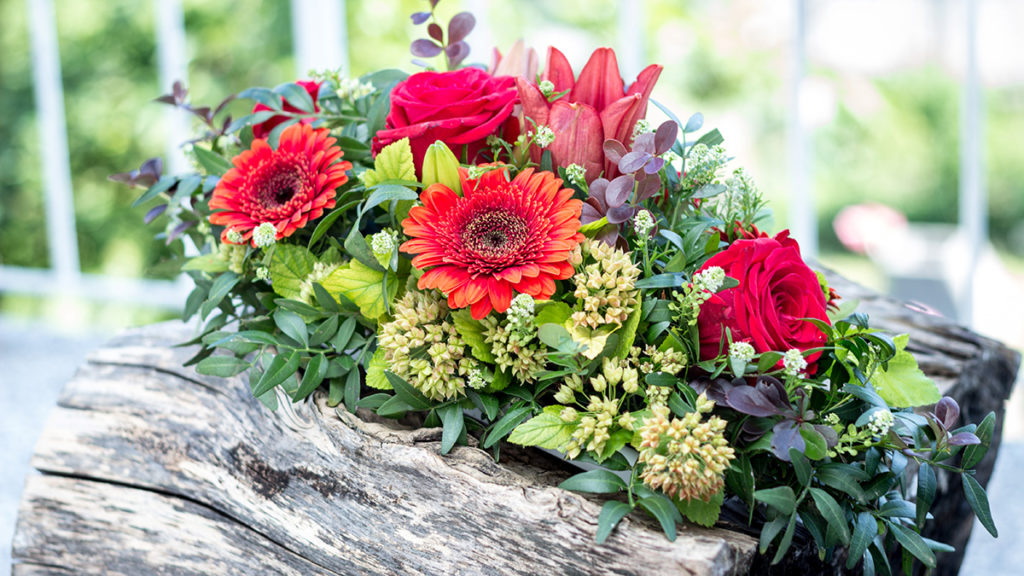 Floral arrangements for a funeral should be colorful and joyful. This photo shows colorful flowers and greenery on a memorial log.