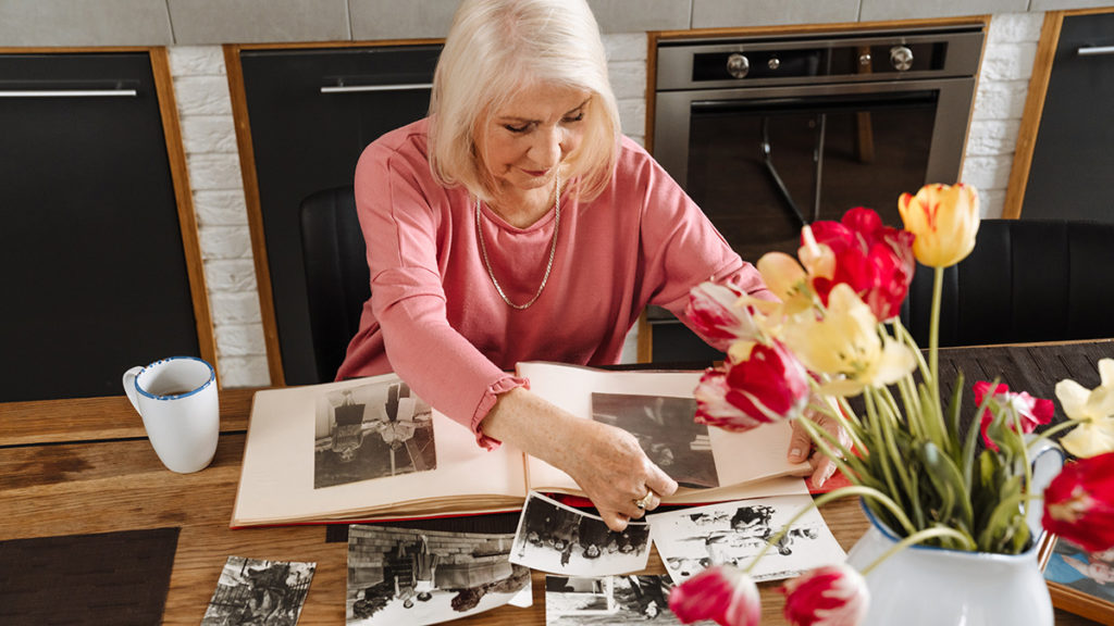 The importance of remembrance: In this photo, An elderly woman looks through photos of deceased friends.