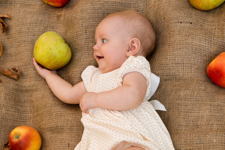 Photo of a baby holding an apple, a popular fruit to celebrate September birthdays.