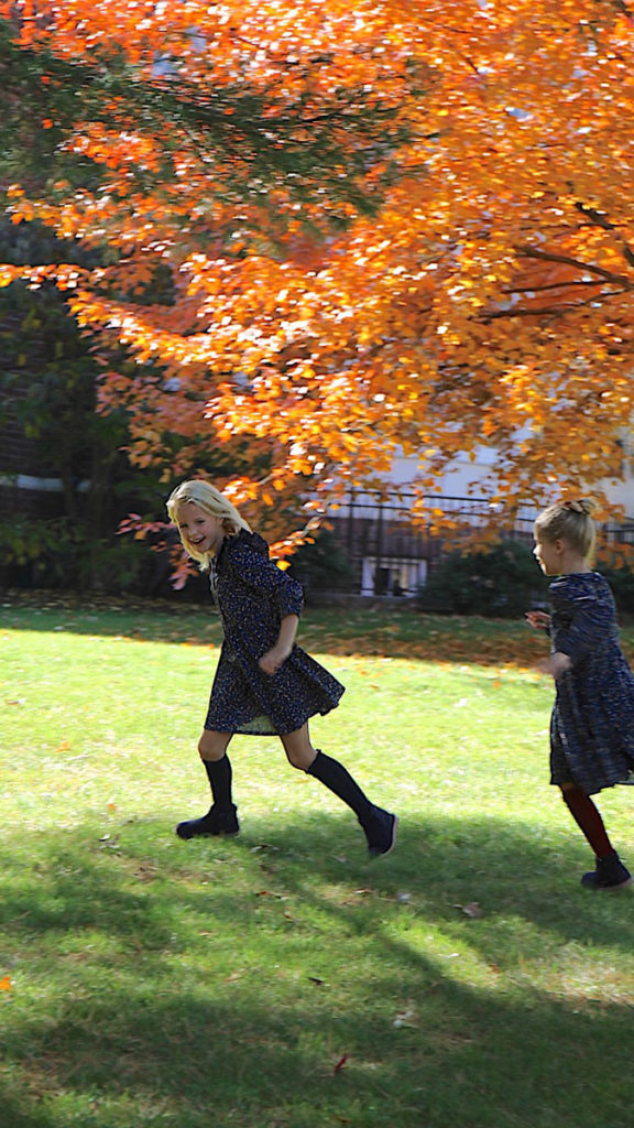 A photo of two girls playing amid autumnal trees and loving fall.