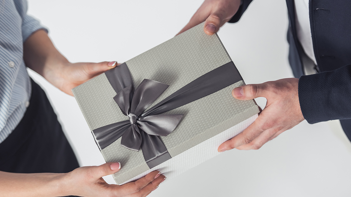 A photo of two business people exchanging workplace gifts