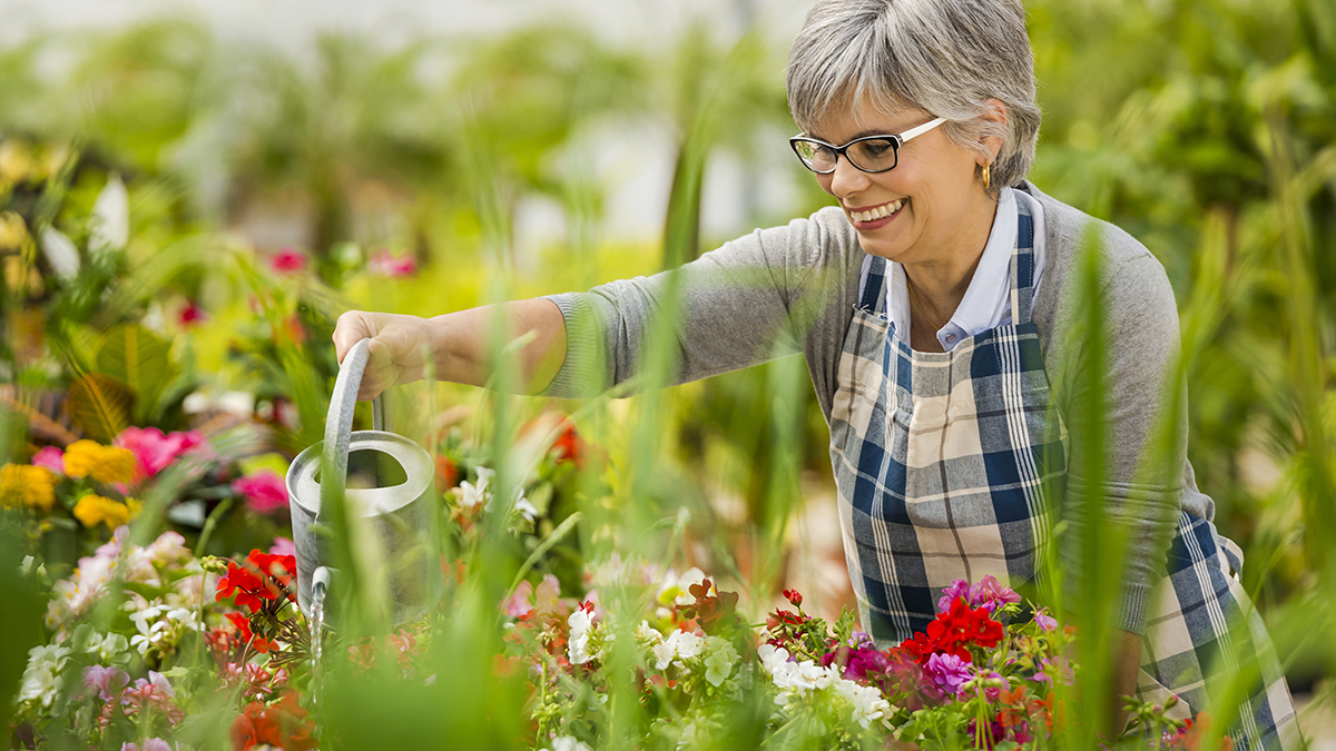 Photo of woman watering plants at a memory garden that help people with dementia.
